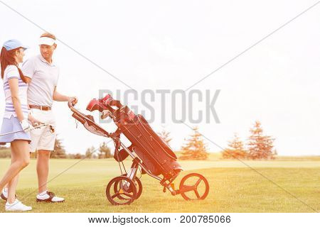 Friends with equipment talking while walking at golf course against clear sky