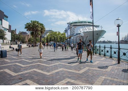 SYDNEY,NSW,AUSTRALIA-NOVEMBER 20,2016: Tourists walking along the Circular Quay waterfront with cruise ship and  view of the Opera House and Sydney Harbour Bridge in Sydney, Australia.