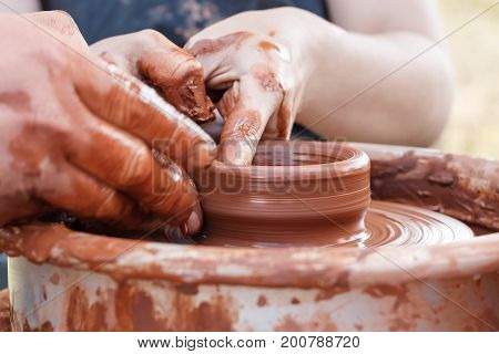 Teaching pottery. A carftman's hands guiding a child hand, showing how to throw a clay pot on a potters wheel. Teacher and learner concept
