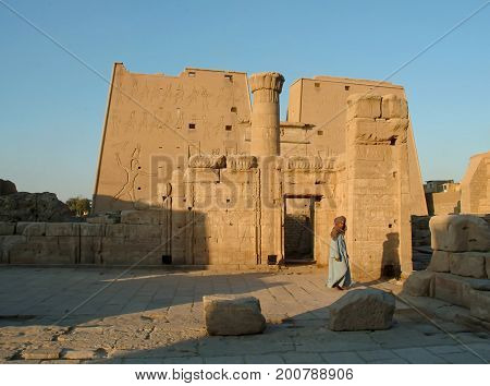 EGYPT, January 15, 2005: Giant pylon at entrance to Horus Temple of Edfu and old Bedouin, Egypt, North Africa, Africa