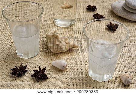Glasses of traditional drink Ouzo or Raki on natural matting with anise star seeds and shells