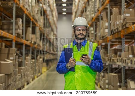 Warehouse worker in hard hat using mobile phone