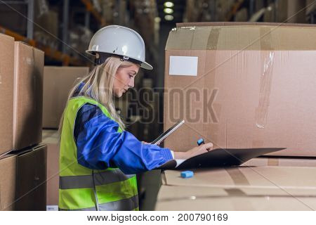 Female warehouse worker making notes in documents near boxes with merchandise