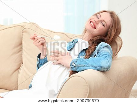 Emotional pregnant woman sitting on sofa and eating ice-cream. Pregnancy hormones concept