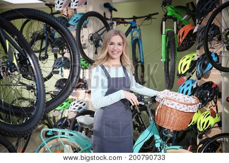 Young pretty woman in bicycle shop