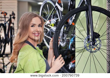Young female seller in bicycle shop
