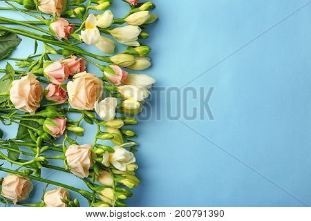 Composition of beautiful roses and freesia flowers on blue background