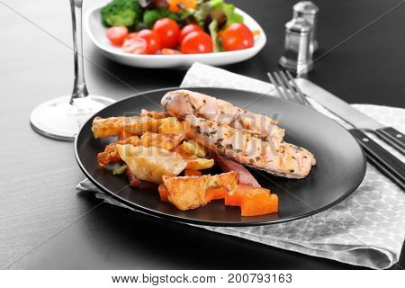 Plate of grilled chicken meat and vegetables on table