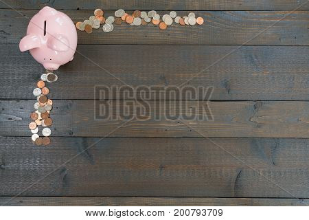 Pink piggy bank surrounded by loose coins or money