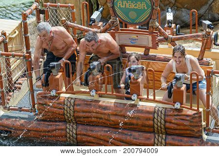 PORT AVENTURA/ SPAIN - MAY 29, 2017. Happy family during the water gun battle on the water attraction Angkor, located in the area of China of the theme park Port Aventura. Salou, Catalonia, Spain.