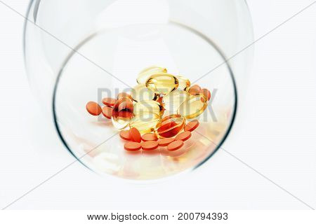 Red Pills And Capsules Of Cod-liver Oil In Glass