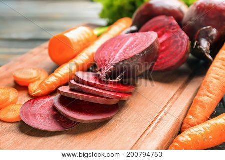 Fresh young sliced beets and carrots on wooden board
