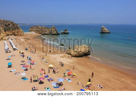Dona Ana Beach in Lagos, Algarve region, south Portugal, Europe. One of the most beautiful beaches in the world. Summer scene, people sunbathing and swimming in Atlantic ocean with empty copyspace