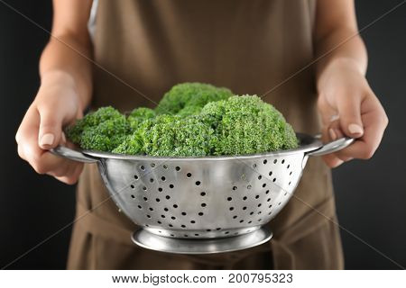 Hands holding colander with fresh green broccoli close-up