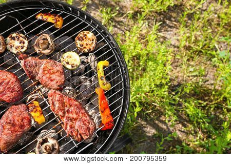 Tasty beefsteaks and vegetables cooking on barbecue grill outdoors