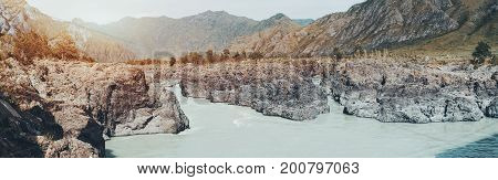 Wide panoramic view of Katun river in its most narrow area Altai mountains Russia: multiple rocks of stony shore peaks of hills in distance pine trees meadows low turbid water of river