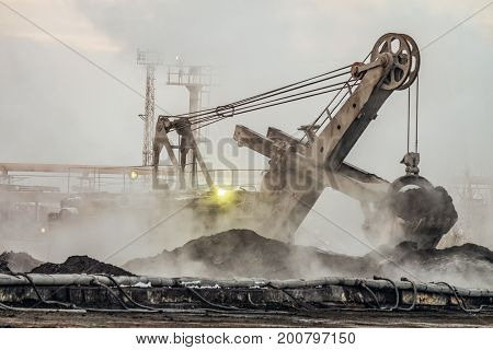 Big bucket excavator works in a outdoors dust dump. Industrial background.