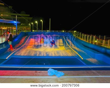 Barcelona, Spain - September 9, 2015: The people resting at cruise ship Allure of the Seas at Barcelona, Spain on September 9, 2015. The ship by Royal Caribbean International. Exterior views of the ship - amusement artificial wave at night