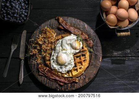 rustic breakfast of blueberry waffles, bacon with eggs
