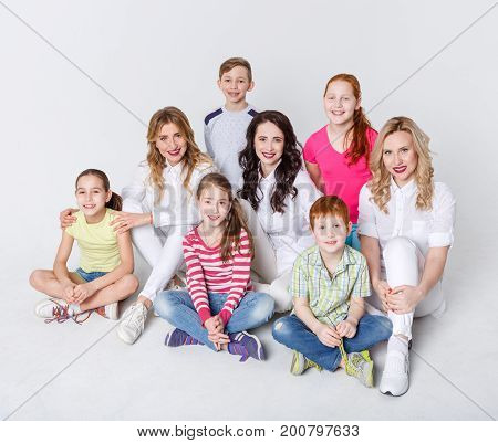 Happy kids and adults sitting on studio studio floor at white background. Group of children and three young attractive women, laughing and posing to camera on white studio background, copy space