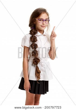 Young smiling genious schoolgirl in glasses pointing up