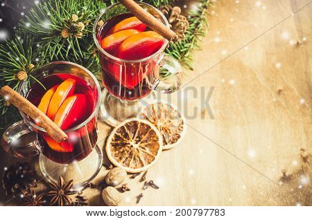Two Glasses with Mulled Wine Spices and Christmas Tree Branches on wooden background. Vintage Toned and Drawn Snow Falling Effect. Selective Focus.