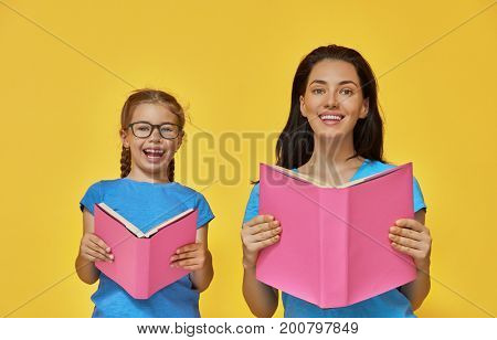 Back to school! Happy cute industrious child and her mother are reading the books indoors. Kid and adult on background of bright wall. Yellow, pink and blue color.