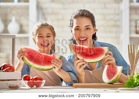 Healthy food at home. Happy family in the kitchen. Mother and child daughter are preparing the vegetables and fruit.