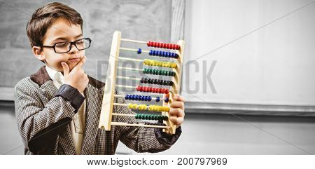 Pupil dressed up as teacher holding abacus in classroom