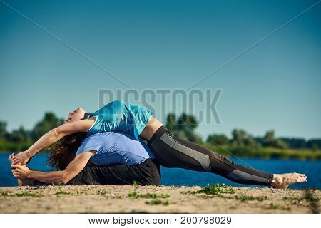 Fit healthy man and woman doing pair yoga outdoor