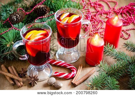 Two Glasses with Mulled Wine Red Candles Spices and Christmas Tree Branches on wooden background. Xmas Postcard. Selective Focus.