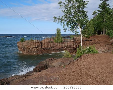 Blue waters of Lake Superior splash against the rockbound shore of Presque Isle Park in Marquette in the upper peninsula of Michigan. poster