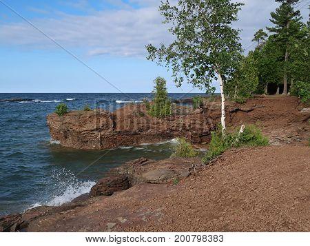 Blue waters of Lake Superior splash against the rockbound shore of Presque Isle Park in Marquette in the upper peninsula of Michigan.
