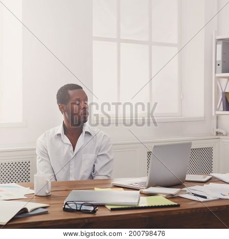 Thoughtful young black businessman in modern white office, lifestyle portrait