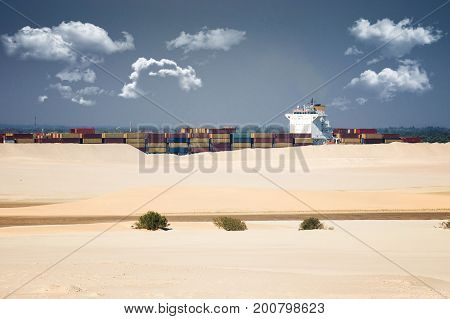 desert ship - freightship traverses the Suez Canal in the direction of the Red Sea observed from a ship that is traveling in the opposite direction on the newly opened expansion canal