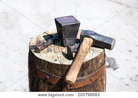 The old tools of a blacksmith on a large wooden stump