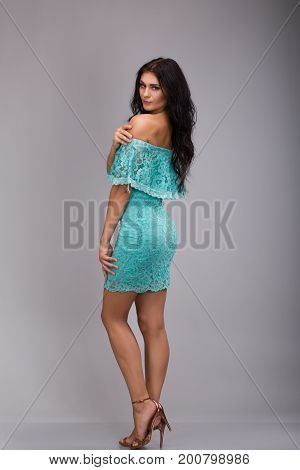 Portrait of young beautiful woman with curly shaggy hair style with smoky eyes make-up dressins in blue dress staying on gray background