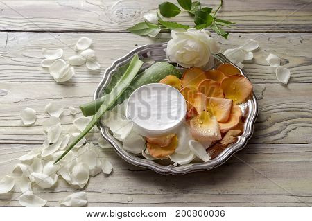 Jar with aloe vera cream, rose petals and aloe vera leaves on a wooden table close-up