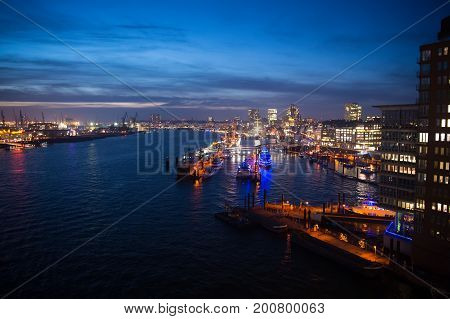 Sea port with ships and cranes in Hamburg Germany with light illumination at night. Harbor or dock with blue water on skyline background. Logistic and shipping concept