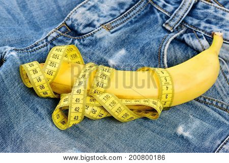 Mens denim pants crotch with banana imitating male genitals. Jeans zipper and pocket close up. Health and male sexuality concept. Banana wrapped with yellow measure tape on jeans selective focus.