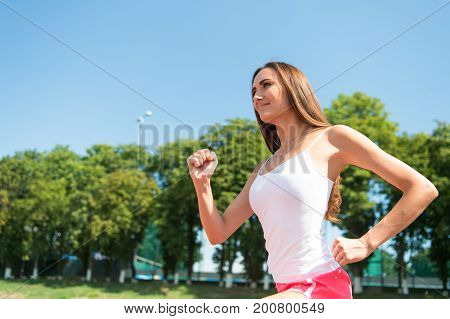 Coach or trainer at workout. Girl sunny outdoor on blue sky. Runner on competition and future success. Sport and healthy fitness. Woman running on arena track.