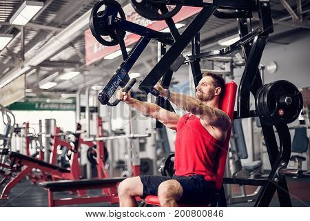 The powerfull athlete doing exercises on pectoral muscles in simulator. Gym Machine.