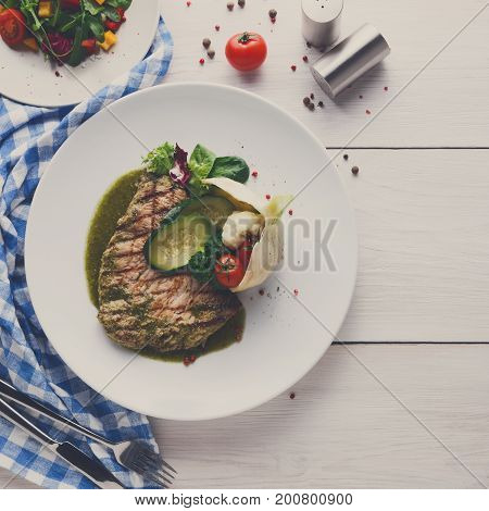 Dining at restaurant. Grilled angus steak with vegetables in fennel and green bell pepper sauce. Healthy food, served on round plate at white wood background and checkered cloth, copy space, top view