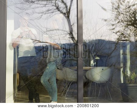 romantic happy young couple enjoying morning coffee by the window in their luxury home