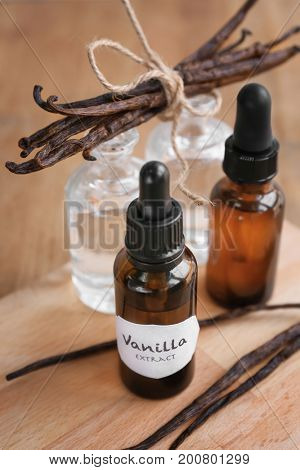 Bottles with aromatic extract and dry vanilla beans on wooden board