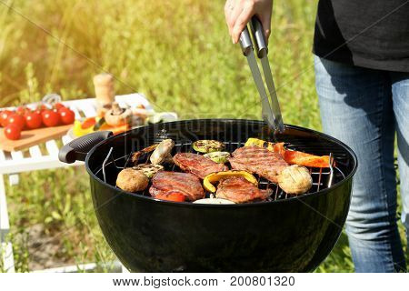 Woman cooking tasty beefsteaks and vegetables on barbecue grill, outdoors