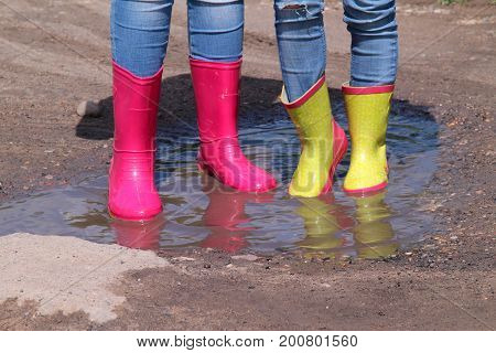 Children's legs in jeans in bright rubber boots standing in a puddle in the sun.