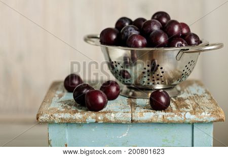 Ripe plums in a colander on a wooden background. Selective focus.