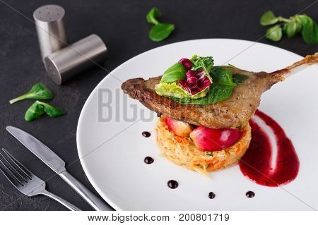 Exclusive restaurant meals. Duck confit with braised cabbage, baked apple and cranberry sauce served on snow white plate on black table background, copy space