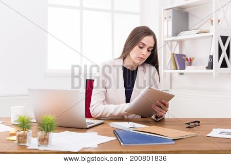 Confident young business woman in formalwear working on digital tablet while sitting at office